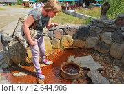 Женщина пьет из источника с минеральной водой в Долине Нарзанов. Приэльбрусье. (2015 год). Редакционное фото, фотограф Инесса Гаварс / Фотобанк Лори