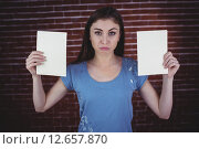 Pretty brunette holding two pages. Стоковое фото, агентство Wavebreak Media / Фотобанк Лори