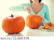 Купить «close up of woman with pumpkins at home», фото № 12669578, снято 17 сентября 2014 г. (c) Syda Productions / Фотобанк Лори