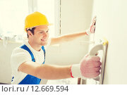 Купить «smiling builder with grinding tool indoors», фото № 12669594, снято 25 сентября 2014 г. (c) Syda Productions / Фотобанк Лори