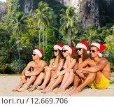 Купить «group of friends in santa helper hats on beach», фото № 12669706, снято 3 августа 2014 г. (c) Syda Productions / Фотобанк Лори