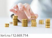 Купить «close up of female hand putting coins into columns», фото № 12669714, снято 2 июля 2015 г. (c) Syda Productions / Фотобанк Лори