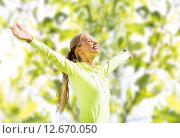 happy woman in sport clothes raising hands. Стоковое фото, фотограф Syda Productions / Фотобанк Лори