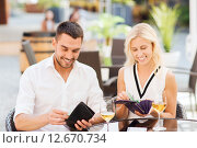 Купить «happy couple with wallet paying bill at restaurant», фото № 12670734, снято 15 июля 2015 г. (c) Syda Productions / Фотобанк Лори
