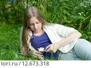 Купить «Девушка гадает на ромашке, лежа на траве», фото № 12673318, снято 5 августа 2015 г. (c) Ирина Новак / Фотобанк Лори
