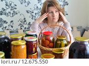 Купить «Уставшая женщина сидит возле банок с домашним консервированием для зимы», фото № 12675550, снято 12 сентября 2015 г. (c) Володина Ольга / Фотобанк Лори