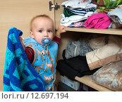 Купить «Мальчик (1 год и 3 месяца) достает вещи из шкафа», эксклюзивное фото № 12697194, снято 7 сентября 2015 г. (c) Вячеслав Палес / Фотобанк Лори