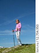 Купить «Молодая женщина с трекинговыми палками на фоне яркого синего неба», фото № 12704950, снято 3 июля 2014 г. (c) Юлия Кузнецова / Фотобанк Лори