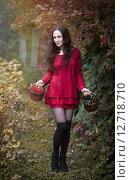 Стройная длинноногая девушка в коротком красном платье держит корзины с ягодами на фоне осенней листвы. Стоковое фото, фотограф Андрей Шарашкин / Фотобанк Лори