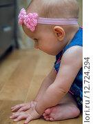 Купить «Восьми месячный ребенок сидит на полу», фото № 12724294, снято 4 сентября 2015 г. (c) Анастасия Улитко / Фотобанк Лори