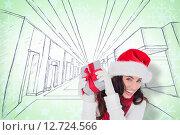 Купить «Composite image of happy brunette in santa hat holding gift», фото № 12724566, снято 25 июня 2019 г. (c) Wavebreak Media / Фотобанк Лори