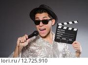 Купить «Young cheerful man with clapperboard and microphone», фото № 12725910, снято 25 декабря 2013 г. (c) Elnur / Фотобанк Лори