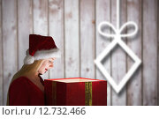 Купить «Composite image of festive blonde holding a gift», фото № 12732466, снято 25 июня 2019 г. (c) Wavebreak Media / Фотобанк Лори