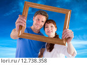 Купить «Composite image of couple holding frame ahead of them», фото № 12738358, снято 24 февраля 2019 г. (c) Wavebreak Media / Фотобанк Лори