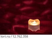 Свеча на красной ткани. Стоковое фото, фотограф Юрий Прокопьев / Фотобанк Лори