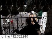Мужчина звонит в колокола на звоннице Даниловского ставропигиального мужского монастыря в городе Москве (2015 год). Редакционное фото, фотограф Николай Винокуров / Фотобанк Лори