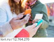Купить «close up of friends with smartphones outdoors», фото № 12764270, снято 19 марта 2015 г. (c) Syda Productions / Фотобанк Лори
