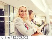 Купить «happy young women in mall or business center», фото № 12765002, снято 3 ноября 2014 г. (c) Syda Productions / Фотобанк Лори
