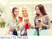 Купить «happy women with smartphones and shopping bags», фото № 12765022, снято 3 ноября 2014 г. (c) Syda Productions / Фотобанк Лори