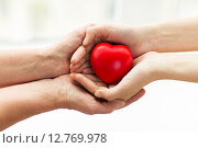 Купить «senior and young woman hands holding red heart», фото № 12769978, снято 10 июля 2015 г. (c) Syda Productions / Фотобанк Лори