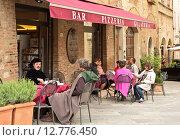 Купить «Посетители кафе в маленьком городке Монтепульчано, Тоскана, Италия», фото № 12776450, снято 16 мая 2014 г. (c) Наталья Волкова / Фотобанк Лори