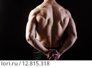 Купить «Muscular man posing in dark studio», фото № 12815318, снято 14 мая 2015 г. (c) Elnur / Фотобанк Лори