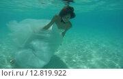 Купить «Невеста в свадебном платье позирует под водой, Индийский океан, Мальдивские острова», видеоролик № 12819922, снято 2 октября 2015 г. (c) Некрасов Андрей / Фотобанк Лори