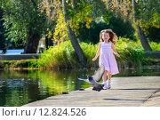 Маленькая девочка играет с голубями в парке возле пруда. Стоковое фото, фотограф Скулков Павел Олегович / Фотобанк Лори
