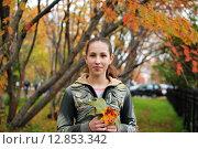 Купить «Девочка с кленовыми листочками в руках в парке осенью», фото № 12853342, снято 20 сентября 2015 г. (c) Ирина Здаронок / Фотобанк Лори