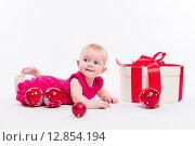 Милая девочка в красном платье лежит на животе среди подарочных коробок. Стоковое фото, фотограф Иван Траймак / Фотобанк Лори
