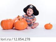 Красивый ребенок в полосатой футболке и пиратской шляпе сидит на полу с тыквами. Стоковое фото, фотограф Иван Траймак / Фотобанк Лори