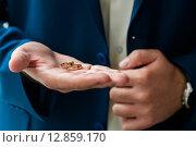 Купить «Свадебные кольца в фокусе лежат на мужской ладони», эксклюзивное фото № 12859170, снято 1 августа 2015 г. (c) Игорь Низов / Фотобанк Лори