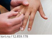 Купить «Жених надевает золотое обручальное кольцо на палец невесте», эксклюзивное фото № 12859178, снято 12 сентября 2015 г. (c) Игорь Низов / Фотобанк Лори