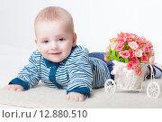 Купить «Маленький улыбающийся мальчик с цветами», фото № 12880510, снято 19 ноября 2018 г. (c) Efanov Aleksey / Фотобанк Лори