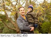 Купить «Young dad lifting his little son in park», фото № 12882450, снято 14 июля 2015 г. (c) Wavebreak Media / Фотобанк Лори