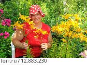 Купить «Женщина с цветами в саду», эксклюзивное фото № 12883230, снято 9 июля 2012 г. (c) Юрий Морозов / Фотобанк Лори