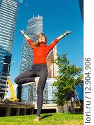 Купить «Йога. Босая девушка стоит на фоне высотных зданий в солнечный день», фото № 12904906, снято 3 октября 2015 г. (c) Сергей Тимофеев / Фотобанк Лори