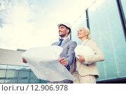 Купить «smiling businessmen with blueprint and helmets», фото № 12906978, снято 19 августа 2014 г. (c) Syda Productions / Фотобанк Лори