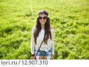 Купить «smiling young hippie woman on green field», фото № 12907310, снято 27 августа 2015 г. (c) Syda Productions / Фотобанк Лори