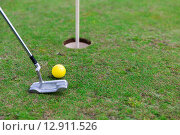 close up of club and ball near hole on golf field. Стоковое фото, фотограф Syda Productions / Фотобанк Лори