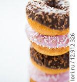 Купить «close up of glazed donuts pile over white», фото № 12912326, снято 21 мая 2015 г. (c) Syda Productions / Фотобанк Лори