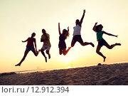 Купить «smiling friends dancing and jumping on beach», фото № 12912394, снято 3 августа 2014 г. (c) Syda Productions / Фотобанк Лори
