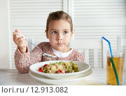 Купить «little girl eating pasta for dinner at restaurant», фото № 12913082, снято 20 сентября 2015 г. (c) Syda Productions / Фотобанк Лори
