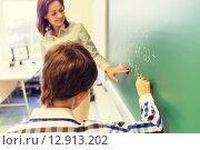 Купить «school boy with teacher writing on chalk board», фото № 12913202, снято 15 ноября 2014 г. (c) Syda Productions / Фотобанк Лори