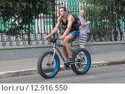 Купить «Москва, мужчина на мощном велосипеде на Елоховской площади», эксклюзивное фото № 12916550, снято 9 июля 2015 г. (c) Дмитрий Неумоин / Фотобанк Лори