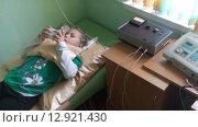 Лечение простуды при помощи электрофореза. Девочка на процедуре прогревания грудной клетки (2015 год). Редакционное видео, видеограф Кекяляйнен Андрей / Фотобанк Лори