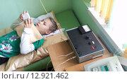 Лечение электрофорезом в детской поликлинике. Девочка играет с телефоном, лежа на кушетке (2015 год). Редакционное видео, видеограф Кекяляйнен Андрей / Фотобанк Лори