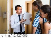 Купить «Debt collector and couple at the doorway», фото № 12927086, снято 19 июля 2019 г. (c) Яков Филимонов / Фотобанк Лори