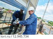 Купить «worker installing facade window», фото № 12945734, снято 29 июня 2015 г. (c) Дмитрий Калиновский / Фотобанк Лори