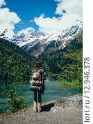 Купить «Девушка-путешественник на фоне гор и озера», фото № 12946378, снято 9 мая 2015 г. (c) Михаил Гордеев / Фотобанк Лори